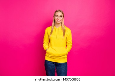 Amazing lady holding hands in pockets of yellow hoodie pullover isolated pink background