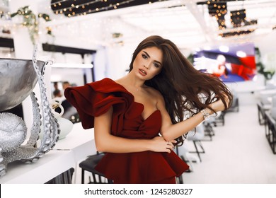 Amazing lady in red party dress with volume sleeve and decollete standing in luxury restaurant. Touching her long dark hair, head tilted on side. Fashion shooting for modern collection. Cozy interior