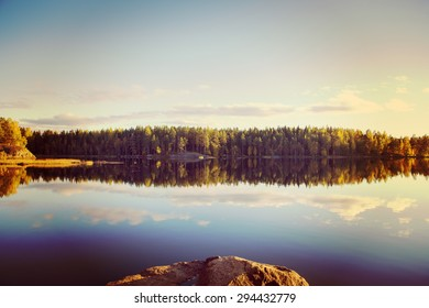 Amazing lake view scenery from Finland during the late night in the summer. Water has a nice reflection. Image has a vintage effect applied.