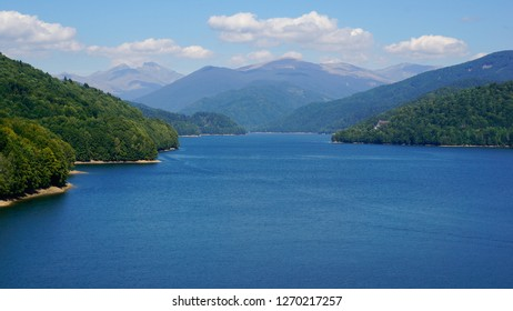 Amazing landscape of an Artificial lake at Vidraru Dam in Arges, Romania. Vast blue waters bordered by mountains covered in green fir trees.