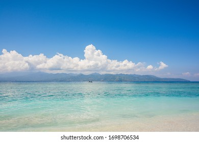 amazing landscape on the beach with sand and blue sky and little clouds in trawangan island in indonesia