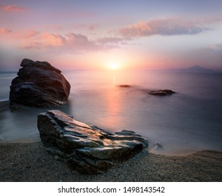 Amazing landscape of sunrise at sea.  Colorful morning view of dramatic sky, seascape and rock. Long exposure image. Greece. Mediterranean Sea. Concept of nature background.