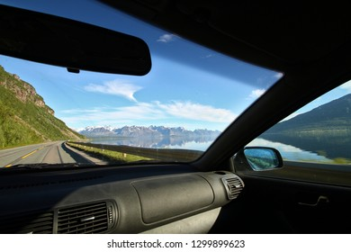 Amazing landscape view from inside the car. Driving on a road between mountains by the ocean on a sunny summer day.