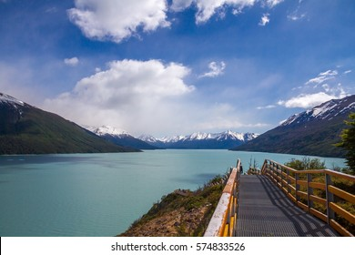 Amazing landscape view on the Argentinian lake (Lago Argentino), snow covered mountains on the back, touristic stairs on the front. Blue sky with beautiful clouds.