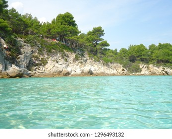 Amazing light blue sea with rocks and green trees in Sithonia, Greece