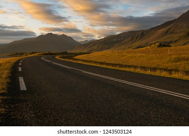 Amazing light in the icelandic landscape of mountains and grass with the road in the East Fjords, Iceland