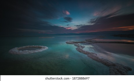 Amazing light and reflections in the Dead Sea during fantastic dawn. Spiritual and mystic atmosphere. Salt formations. Lowest elevation, Ein Gedi, Ein Bokek, south district, Israel. Long exposure.