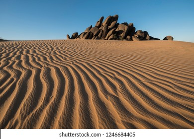 amazing lines at sanddune in Sahara desert with rocks in the background