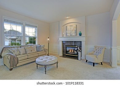 Amazing living room features white mantel and millwork accented with natural stone surround under abstract painting. Pair of tufted accent chairs paired with an ivory ottoman with caster legs