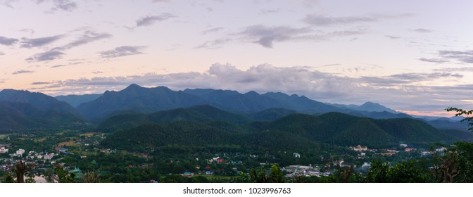 Amazing local city and wild nature view of layer of mountain forest landscape with cloudy sky at winter season. Natural green scenery of cloud and mountain slopes background. Maehongson,Thailand
