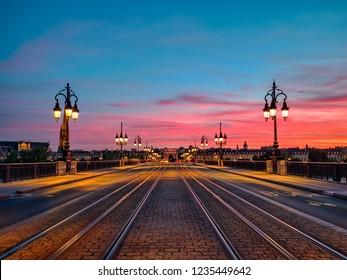 Amazing low angle view of the Bordeaux  Stone Bridge (Pont de Pierre) and amazing sunset sky over the Bordeaux city, France.