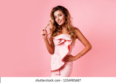 Amazing luxury seductive woman in stylish  pink party dress posing on  rose  wall . Blond  healthy wavy hairs. Fashion portrait.