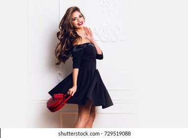 cdc146ddf198 Amazing luxury seductive woman in stylish black party dress posing on white  wall . Red hand