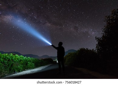 An amazing milky way and stargazing with a silhouette man flashing the light towards the stars. Image contains noise and soft due to high ISO.