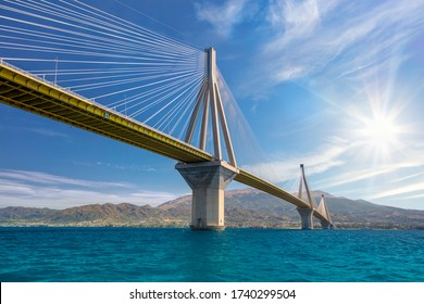 Amazing Modern Bridge against blue sky with sun. Rion-Antirion Bridge. The bridge connecting the cities of Patras and Antirrio, Greece