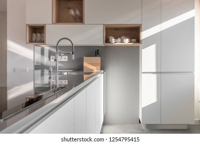Amazing modern kitchen with white walls and gray tiled floor. There are lockers with shelves with dishes, tabletop with a sink with chrome faucets, stove. Sun shines onto them. Horizontal.