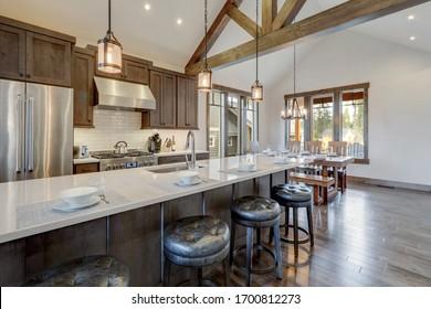 Superbe cuisine luxueuse moderne et rustique avec plafond voûté et poutres en bois, longue île avec comptoir en quarts blancs et armoires en bois foncé.