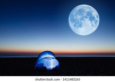 Amazing moon over the sea, beach and lit tent at sunrise
