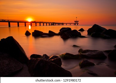 Amazing morning, long exposure make smooth movement, seascape with impressive summer view, Sunrise between black rocks silhouettes over the sea bridge in Burgas bay, Black Sea, Bulgaria.