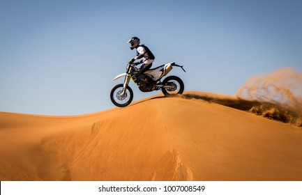 Amazing motor-cross wheelie across the desert. Amazing sand color for fossil rock rocky mountain. Adventure and adrenaline power