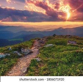 Amazing mountain landscape with colorful vivid sunset on the cloudy sky and path through the rocks, natural outdoor travel background. Beauty world.