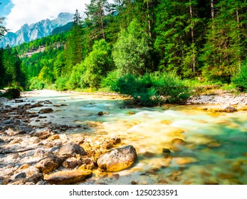 amazing natural landscape, in a beautiful, slightly cloudy day, in the heart of Europe in Slovenia, in Pericnik Park, the clear torrent of water with the mountains in the background