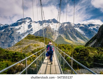 Amazing Nature of Hooker Valley Track in Mount Cook, New Zealand. Young Family walk on Suspension Bridge.
