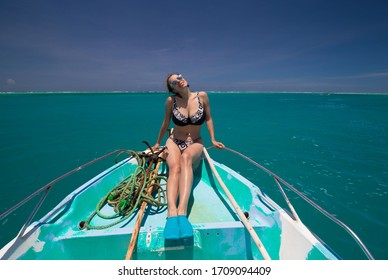 Amazing nature landscape. Beautiful woman, dressed in bikini, has sexy body, enjoys relaxing on boat. Tropical blue sea. Travel in paradise. Inspiring summer. Adventure beach style.