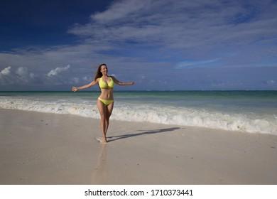 Amazing nature landscape. Beautiful woman, dressed in yellow bikini, has sexy tan body. Fashion tropical blue sea. Travel in paradise. Inspiring hot summer. Erotic female beach style.