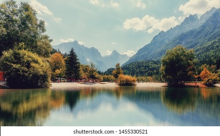 Amazing nature Landscape in Julian Alps during sunset. Lake Jasna near Kranjska Gora, Slovenia. Crystal clear alpine with colorful trees and mountain peaks in background. Triglav national park