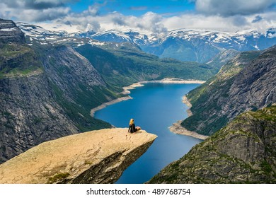 Amazing nature view with Trolltunga and a girl sitting  on it. Location: Scandinavian Mountains, Norway, Odda. Artistic picture. Beauty world. The feeling of complete freedom.