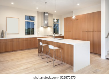 Amazing new contemporary wooden Kitchen with kitchen Island and bar chairs at night.
