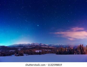 Amazing night landscape. Blue sky full of bright stars. Winter dusk in mountains.