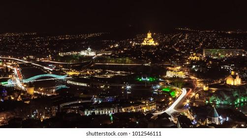 Amazing night panoramic view of Kura (Mtkvari) River, Sameba Holy Trinity Cathedral, Metekhi Church, bridge of Peace and Presidential Palace in old city of Tbilisi, Georgia
