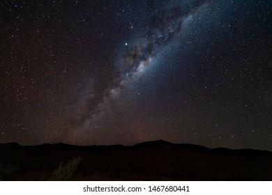 An amazing night sky at Atacama Desert.The milky way over us and Atacama mountains, just an awe nightscape over our base camp inside Atacama arid desert. Amazing view over Sagittarius night stars