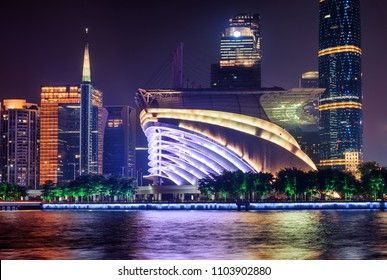 Amazing night view of modern buildings at the Tianhe District of the Zhujiang New Town in Guangzhou, China. Scenic colorful city lights reflected in water of the Pearl River. Wonderful cityscape.