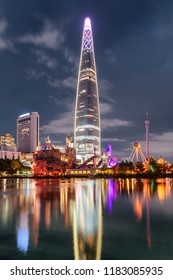 Amazing night view of skyscraper reflected in lake at downtown of a., in South Korea. Scenic modern tower is visible on cloudy sky background. Wonderful cityscape.