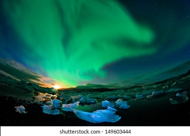 Amazing northern lights performance over glacier lagoon in Iceland during setting moon