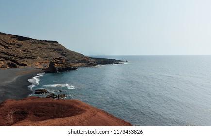 Amazing ocean landscape near vulcano mountain. Background near vulcano. Black and red fantastic sand