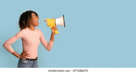 Amazing Offer. Young Black Woman Shouting With Megaphone, Making Announcement, African American Lady With Loudspeaker In Hands Sharing News, Standing Over Blue Background, Panorama, Copy space