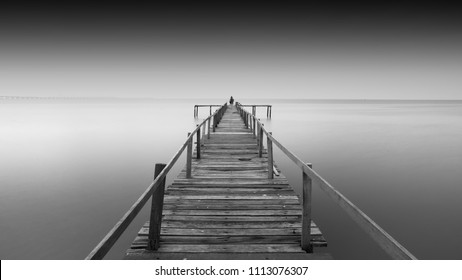 Amazing old abandon wooden jetty in minimalist black and white fine art photography at Teluk Tempoyak, Penang. (blurry soft focus noise grain visible full resolution) Nature composition