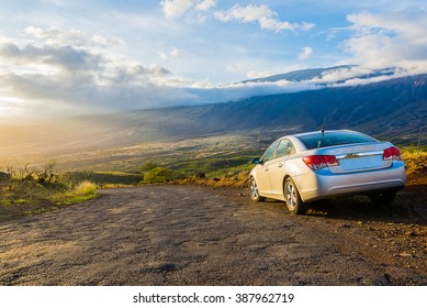 Amazing old road with a car parked on the side and an amazing view of volcano and sunset on the island of Maui, Hawaii.