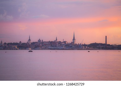 Amazing old Tallinn cityscape from the water at colorful pink sunset