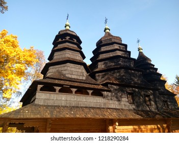 Amazing old wooden church building with wooden shingled roof. Old dark bilding and golden leaves sky background. Fall landscape