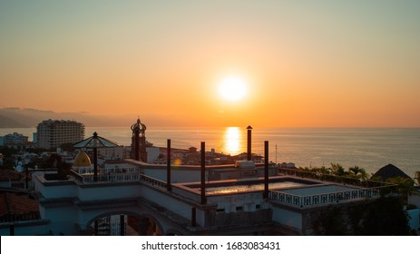Amazing Orange Sunset Over Blue Ocean on a Rooftop view of Old Town in Puerto Vallarta Mexico