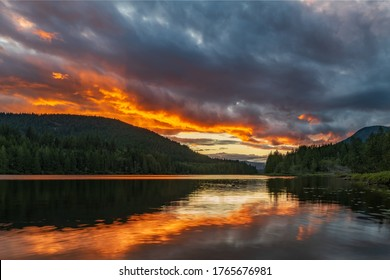 Amazing orange sunset over lake with reflection at Inland Lake Provincial Park on the sunshine coast near Powell River on Inland Lake Provincial park.