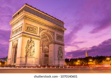 Amazing ornamental monument of Arc de Triomphe illuminated in twilight with violet sky on background in Paris, France
