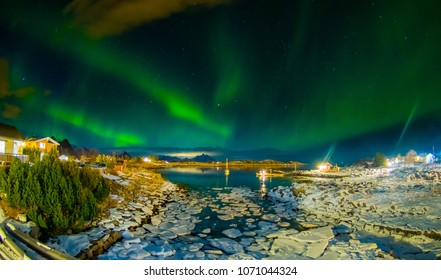 Amazing outdoor view of green aurora borealis in the sky during night and small and medium pieces of Ice left behind during a low tide on a frozen lake