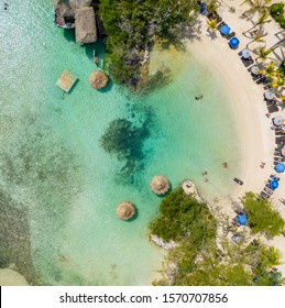 Amazing overhead view of a pristine beach background with emerald water in idyllic Roatan, Honduras. Bird's eye view, aerial view or drone view of a beach with umbrellas and beach chairs.