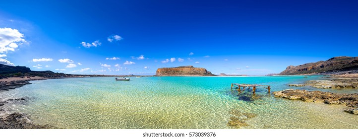 Amazing panorama of Balos Lagoon with magical turquoise waters, lagoons, tropical beaches of pure white sand, small boats, pier and Gramvousa island on Crete, Greece
